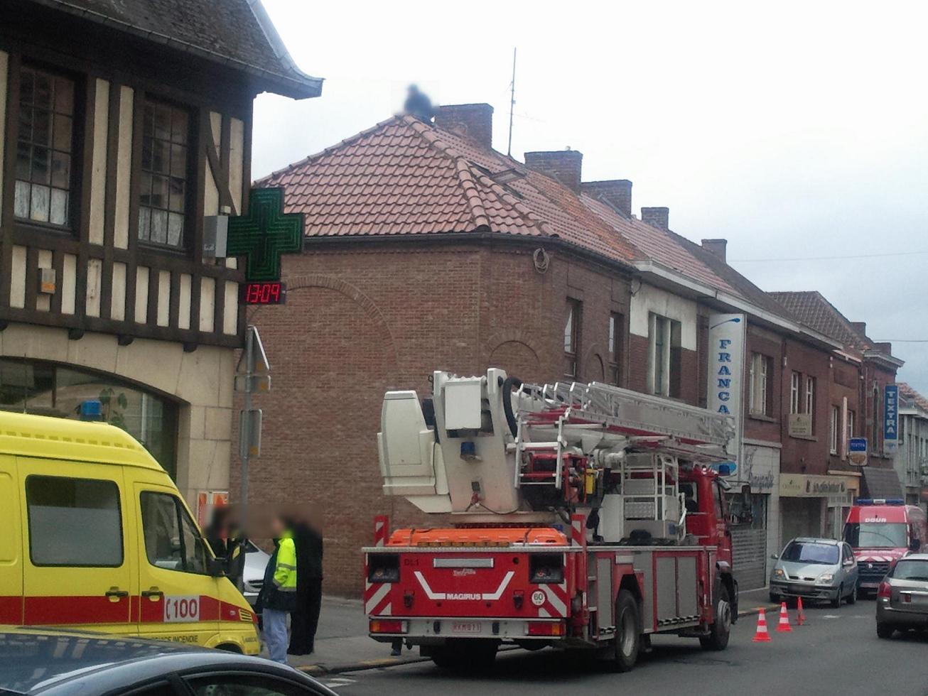 Un jeune homme en haut d'un toit à la place Vandervelde à Dour